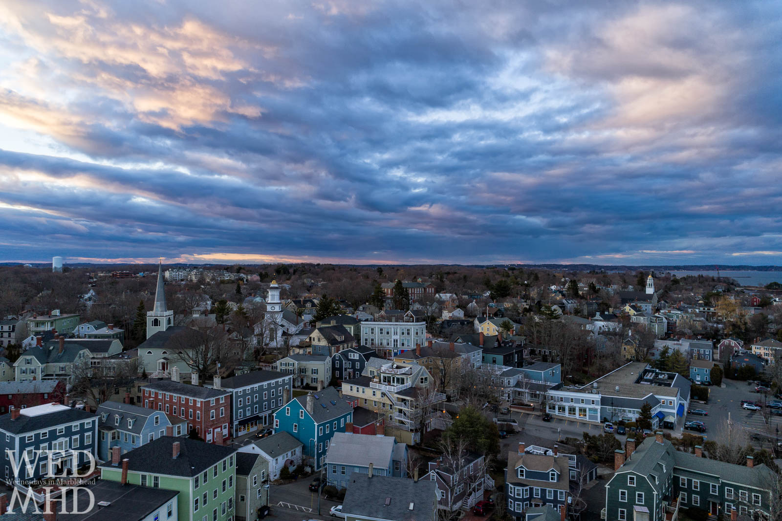 An aerial view of historic downtown Marblehead on a late March evening with a soft sunset reflected in the clouds above