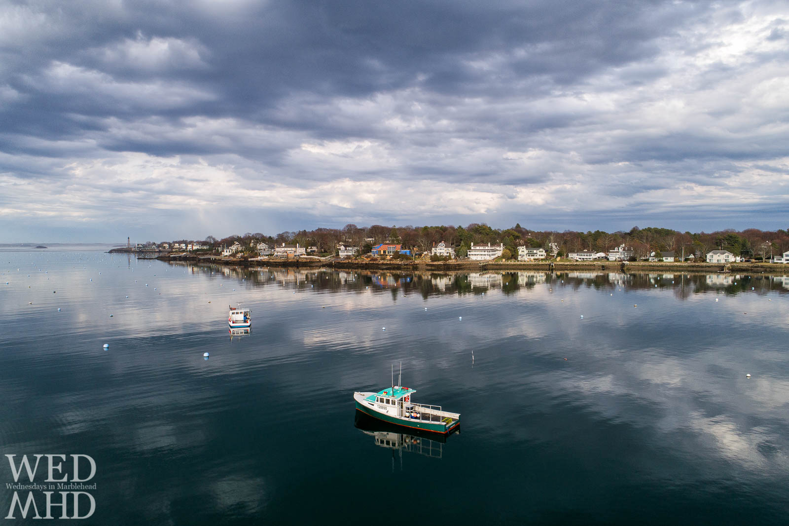 Two lobster boats cast reflections on a still harbor as sunlight casts a glow on Marblehead Neck