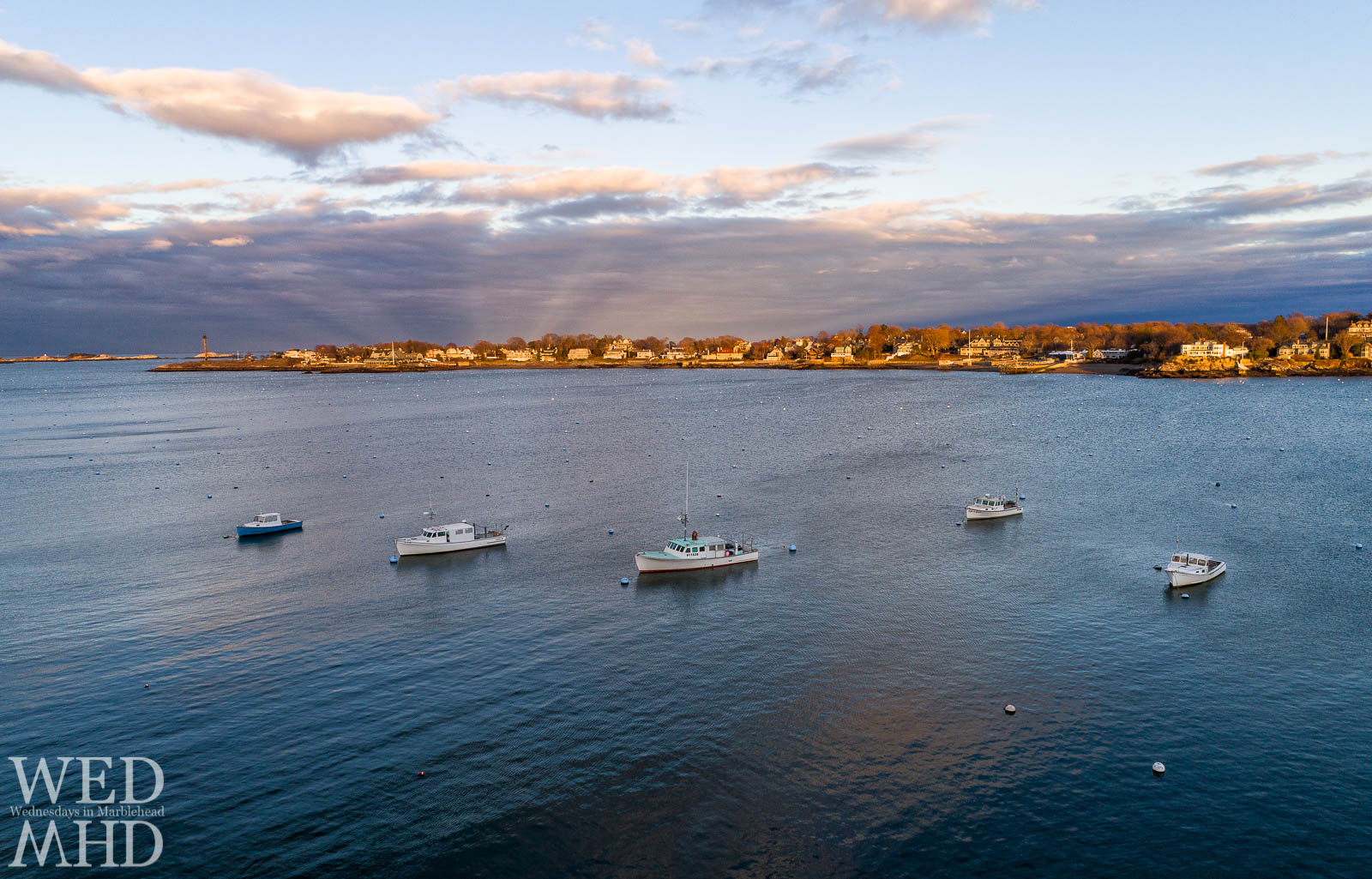 The working boats in Marblehead Harbor are backed by the golden light of sunset reflecting off Marblehead Neck
