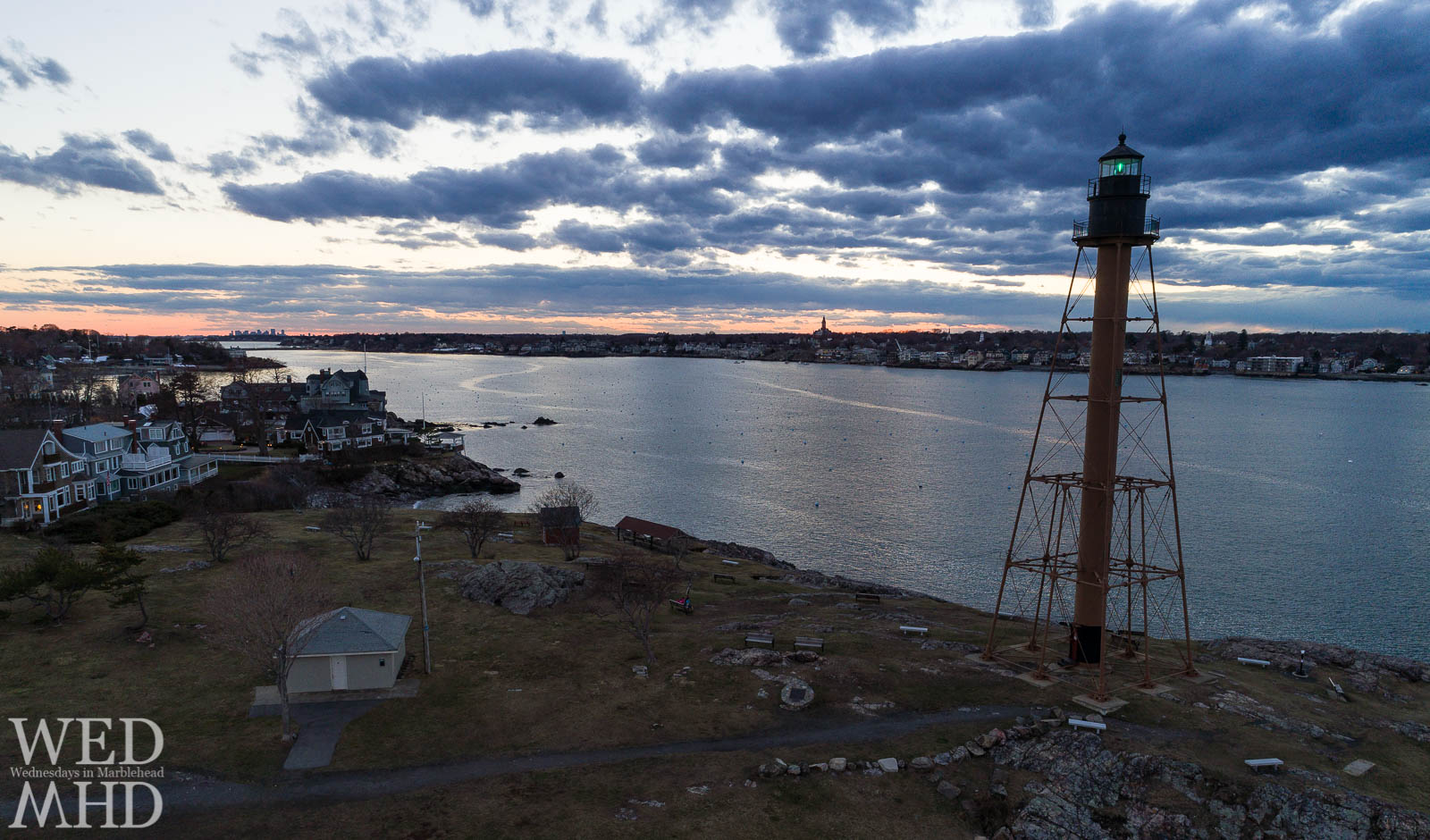 The green beacon of light at Chandler Hovey Park shines against the sunset of a March evening in Marblehead