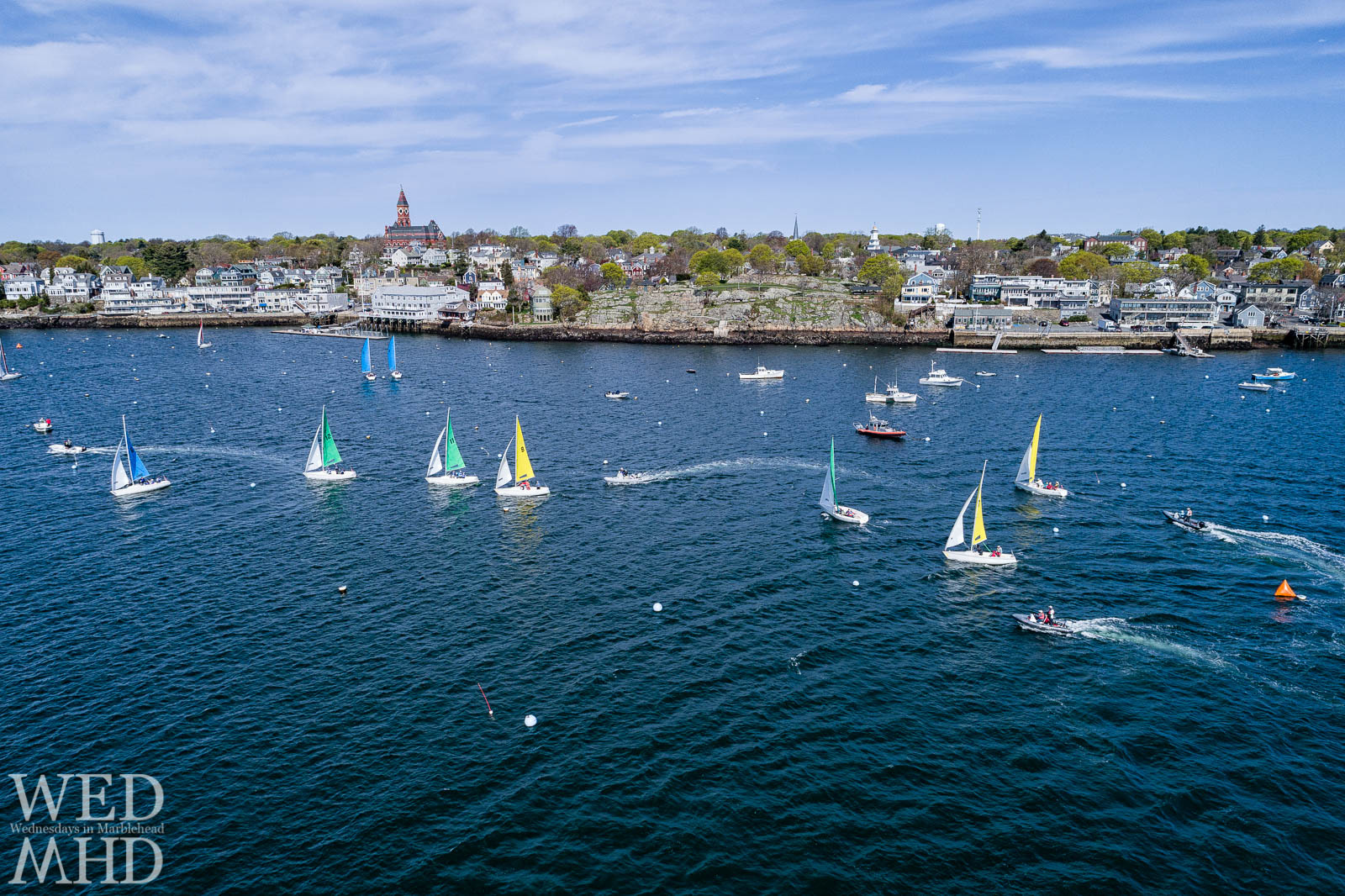 An aerial view of stiff competition during Jackson Cup racing in Marblehead Harbor features boats flying colorful sails as they cross in front of familiar landmarks