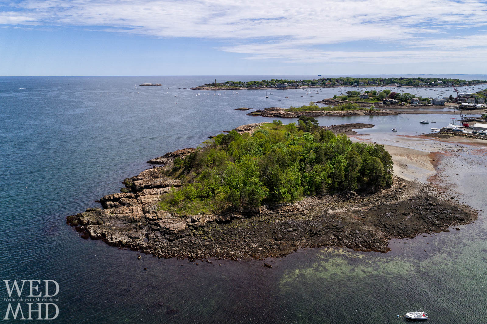 Low tide at Brown's Island captured from above reveals shallow water and an active Marblehead harbor in the distance