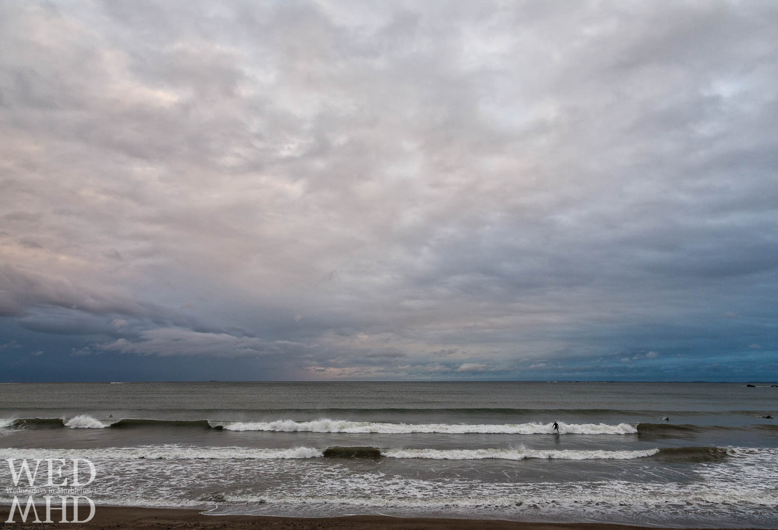 As the rain finally let up, Devereux Beach filled with surfers riding out the storm as clouds broke overhead