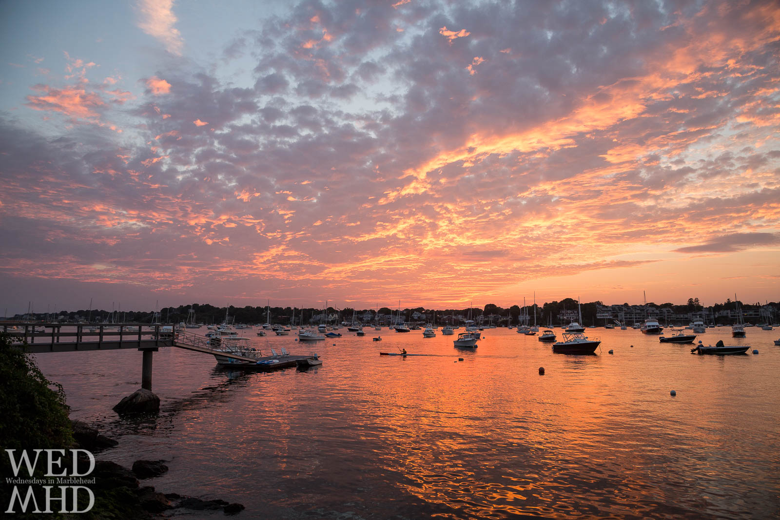 A man in a kayak is captured rowing through Marblehead Harbor as the sunset explodes above and reflects in the still water