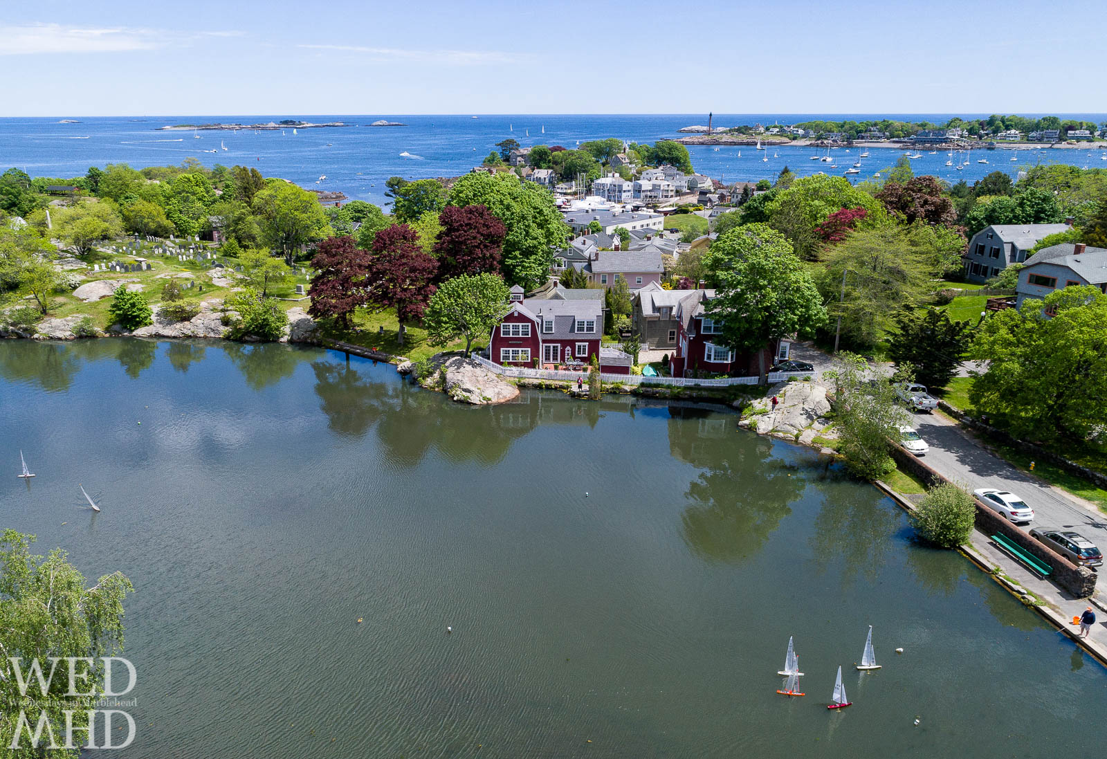 Sailing on Redd's Pond takes place on a beautiful Spring day with more boats seen sailing in the big harbor just beyond
