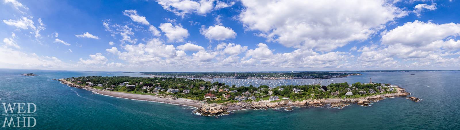 An aerial panorama off the shores of Marblehead Neck captures Castle Rock under the clouds on a perfect Summer afternoon