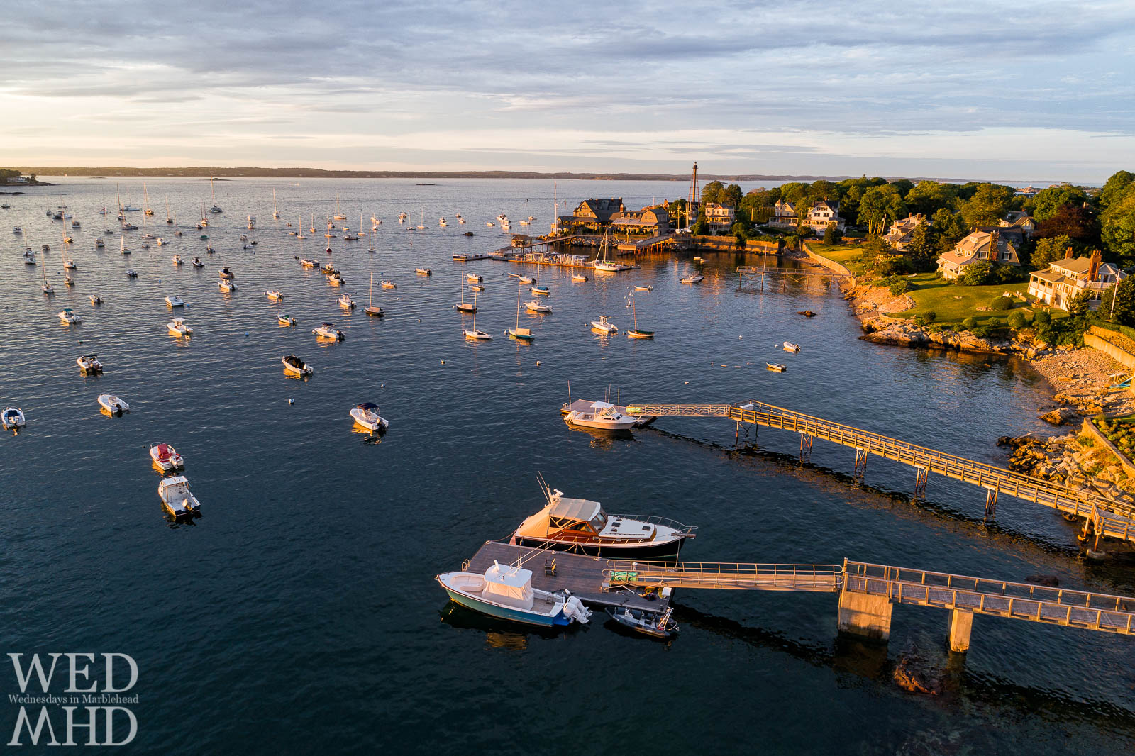 Golden hour creates piers of gold in Marblehead Harbor as the houses, boats and piers are bathed in golden light from the setting sun