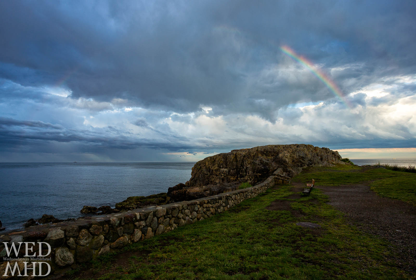 A rainbow forms over Castle Rock between storms on a late June day in Marblehead
