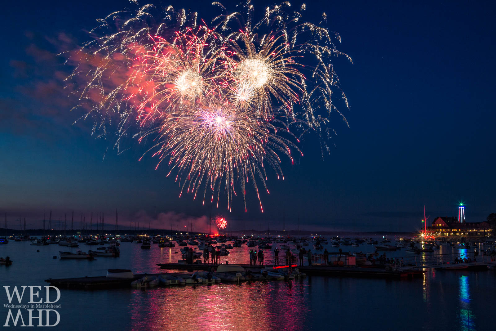 A view of fireworks over Marblehead harbor from the Pleon Yacht Club on Marblehead Neck captures a group of spectators on a float taking in the show