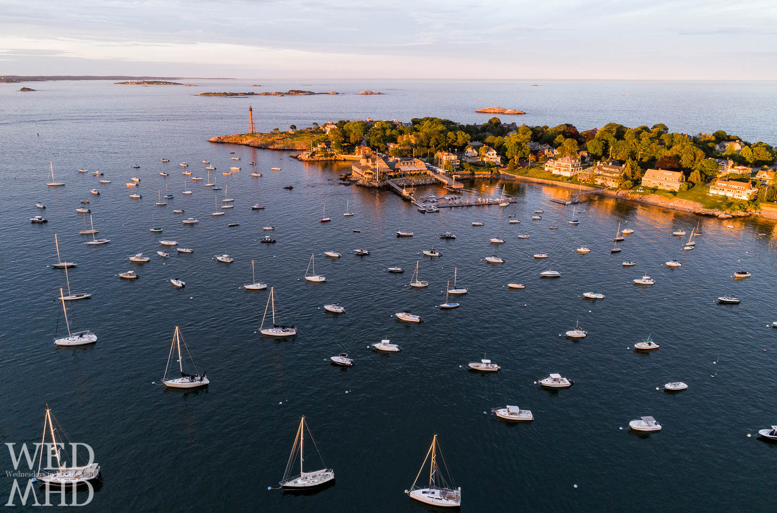 An aerial view of golden masts reflecting the last glow of sunset in Marblehead Harbor with the Neck, Corinthian Yacht Club and lighthouse glowing as well
