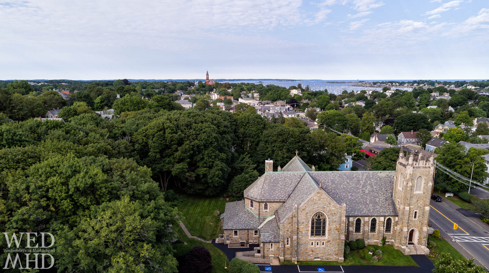 Star of the Sea church in Marblehead is surrounded by trees and flanked by Abbot Hall in the distance as well as Marblehead Harbor