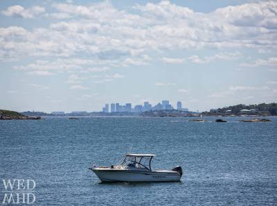 The boat named Sunshine and Daydream is anchored off Marblehead Neck on a Sunday afternoon with clear views of the Boston skyline