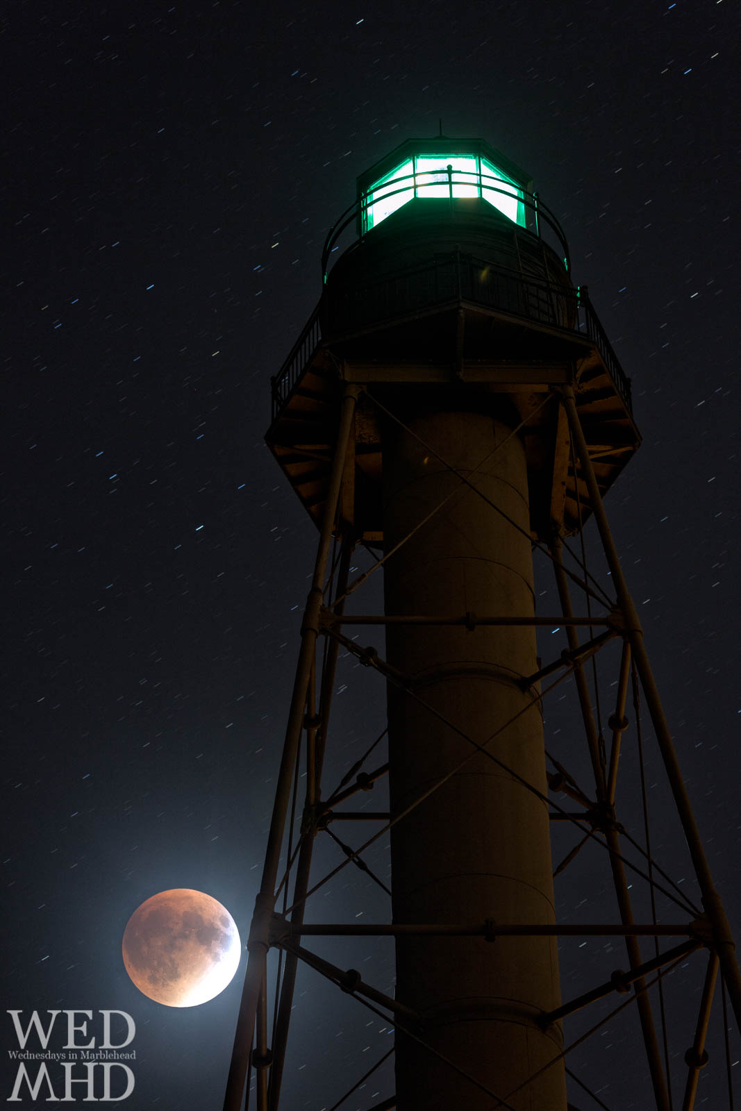 A lunar eclipse takes place in the night sky behind Marblehead Light in September 2015