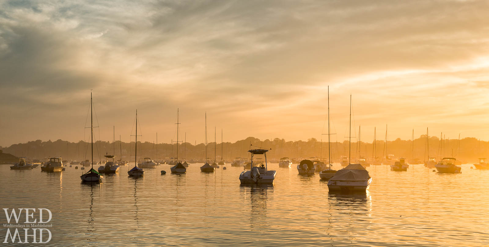 Boats moored in Marblehead seem to float on a golden harbor as the sunset is diffused by evening fog to create a beautiful scene