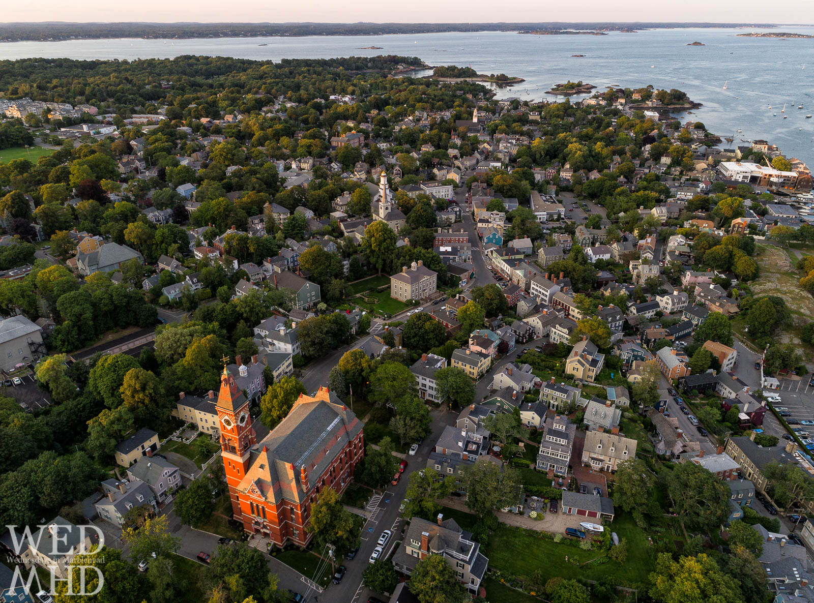 Evening light shines bright on Abbot Hall and historic downtown Marblehead in this aerial view of Old Town with historic homes, churches and shopping a stones throw from the ocean