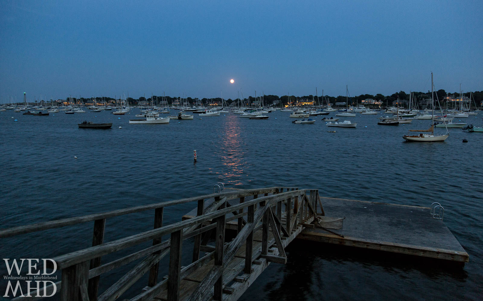 The Crocker Park float and a harbor full of boats are seen on an early September evening as the full corn moon rises