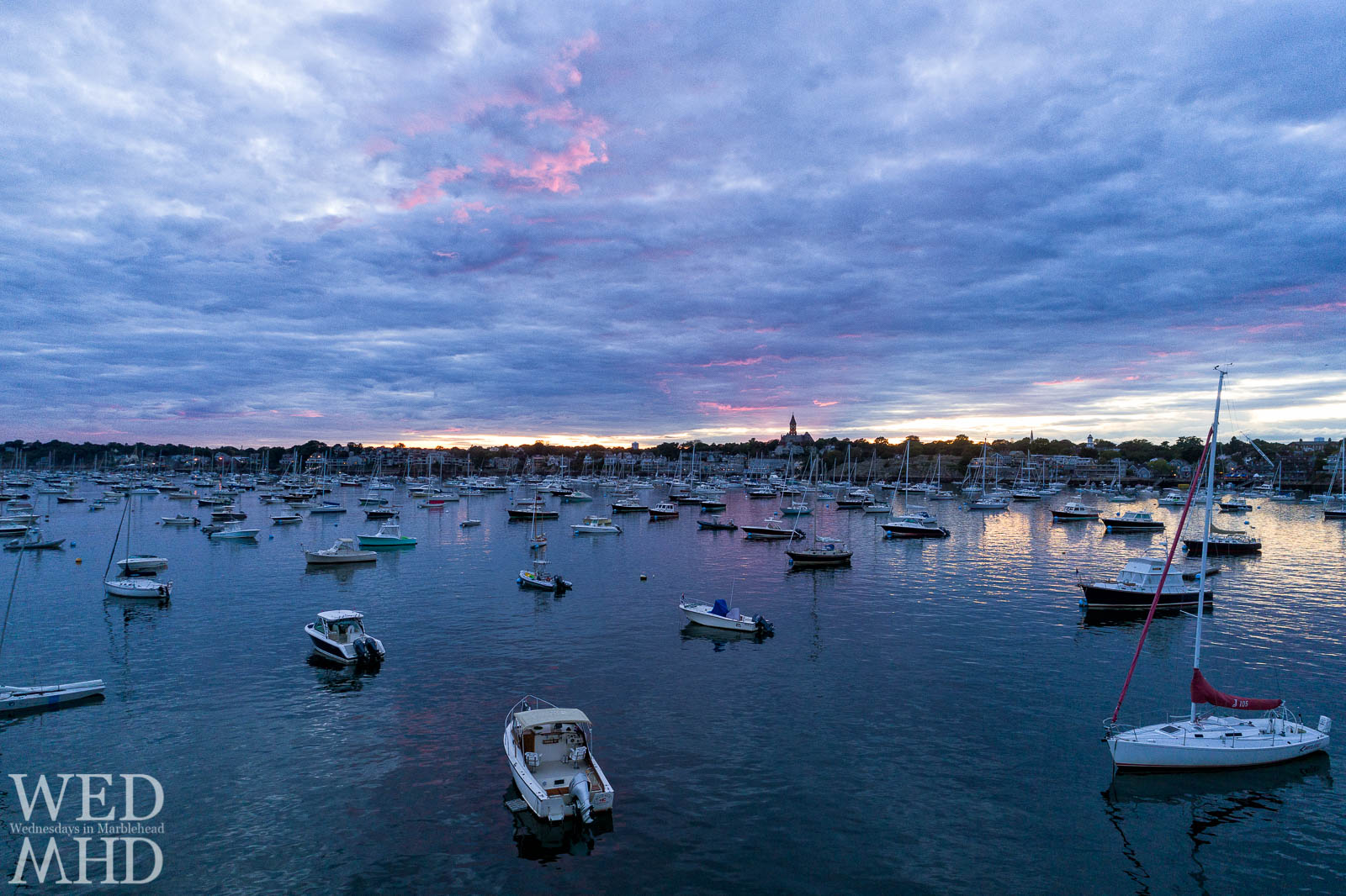 A low aerial view of a mid-harbor sunset reveals pink light behind Abbot Hall and high in the September sky as boats fill their moorings