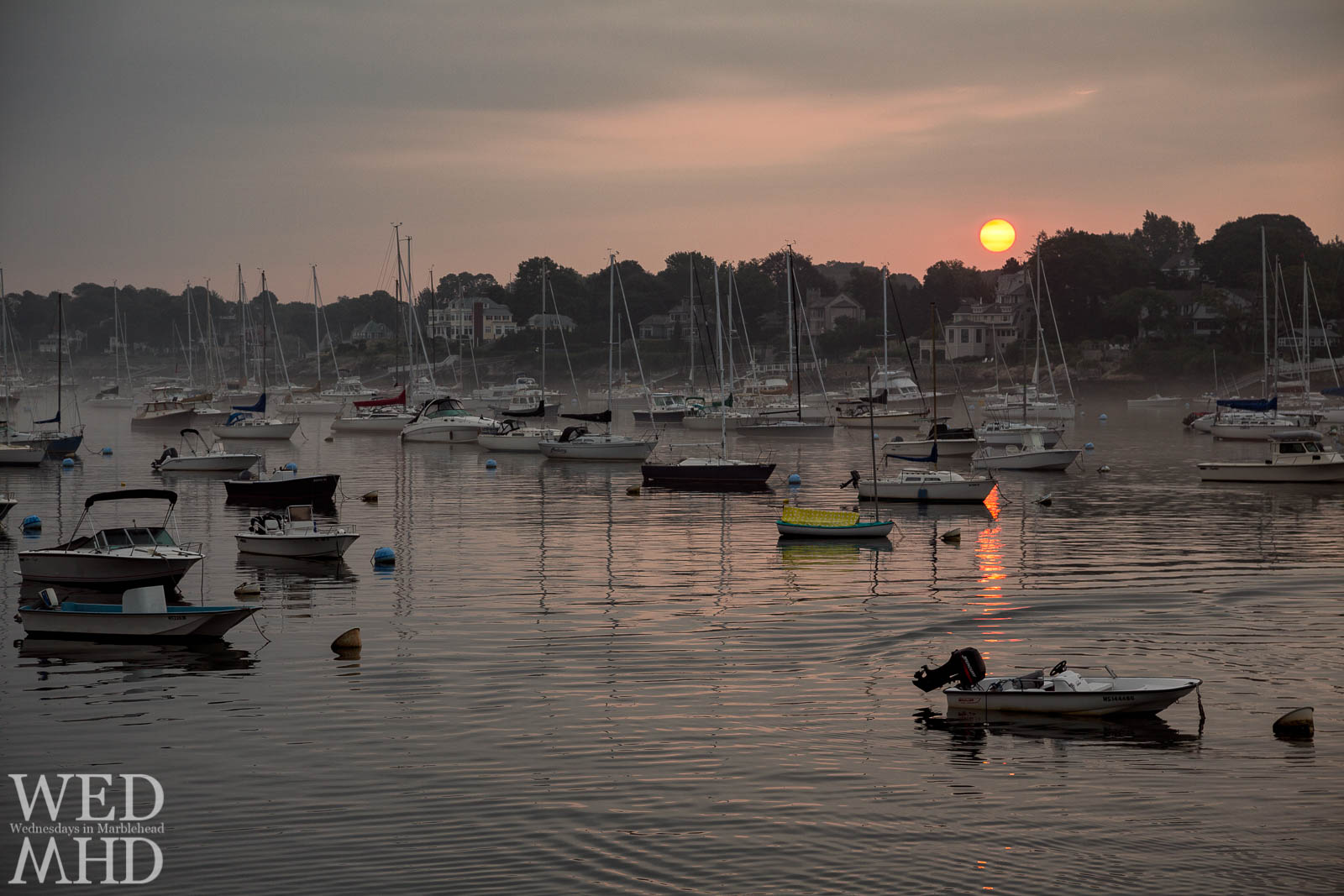 The red sun rising over Marblehead Neck casts its light onto Marblehead Harbor filled with boats as Summer nears its end