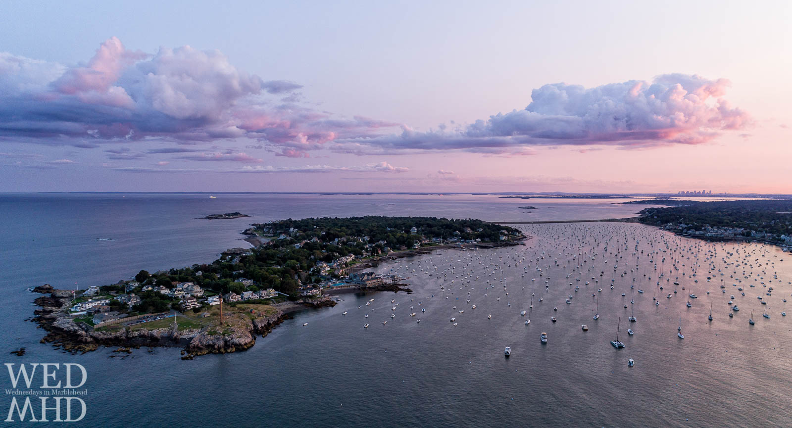 A purple sunset sky over Marblehead harbor bathes the Neck, causeway and boats in a soft light with the Boston skyline visible in the distance
