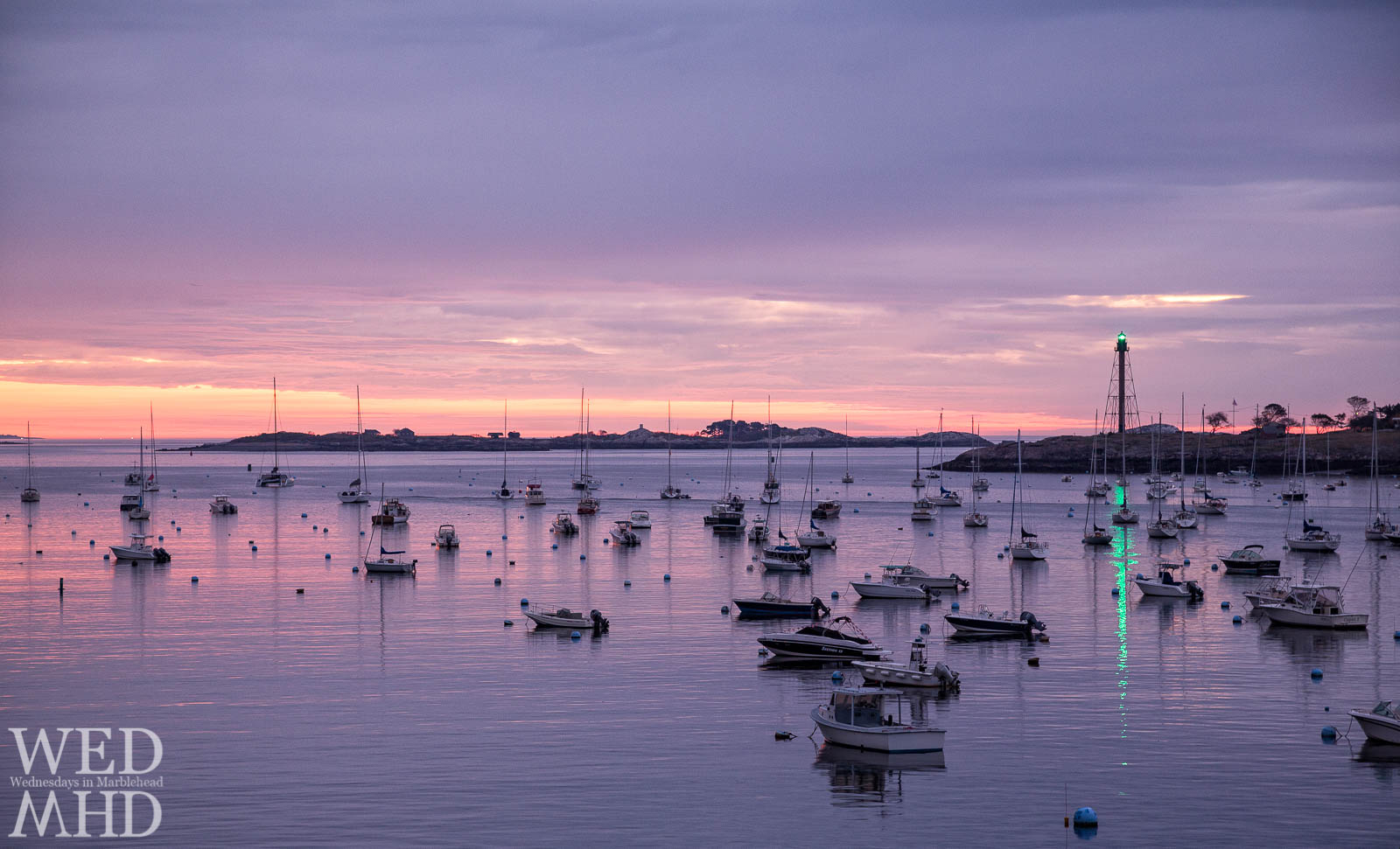 The green beacon atop the lighthouse is reflected in the still waters of the harbor as a new day dawns in Marblehead