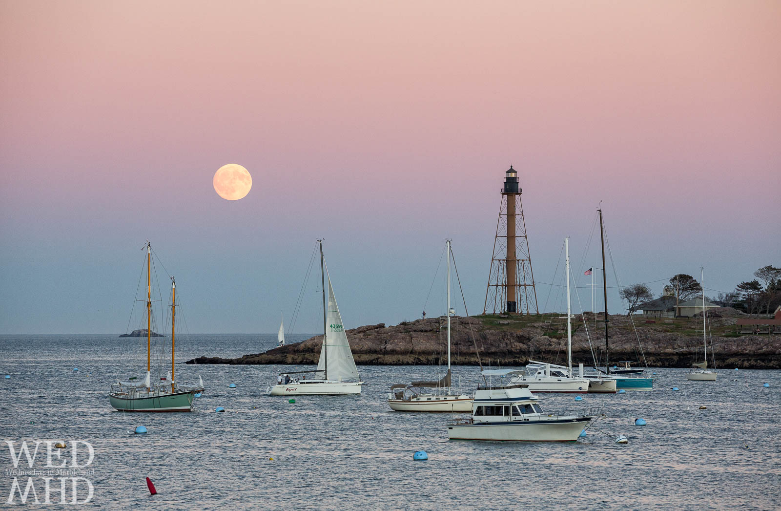 A boat named Expect comes into harbor under the light of the Harvest Moon as seen from Lovis Cove in Marblehead
