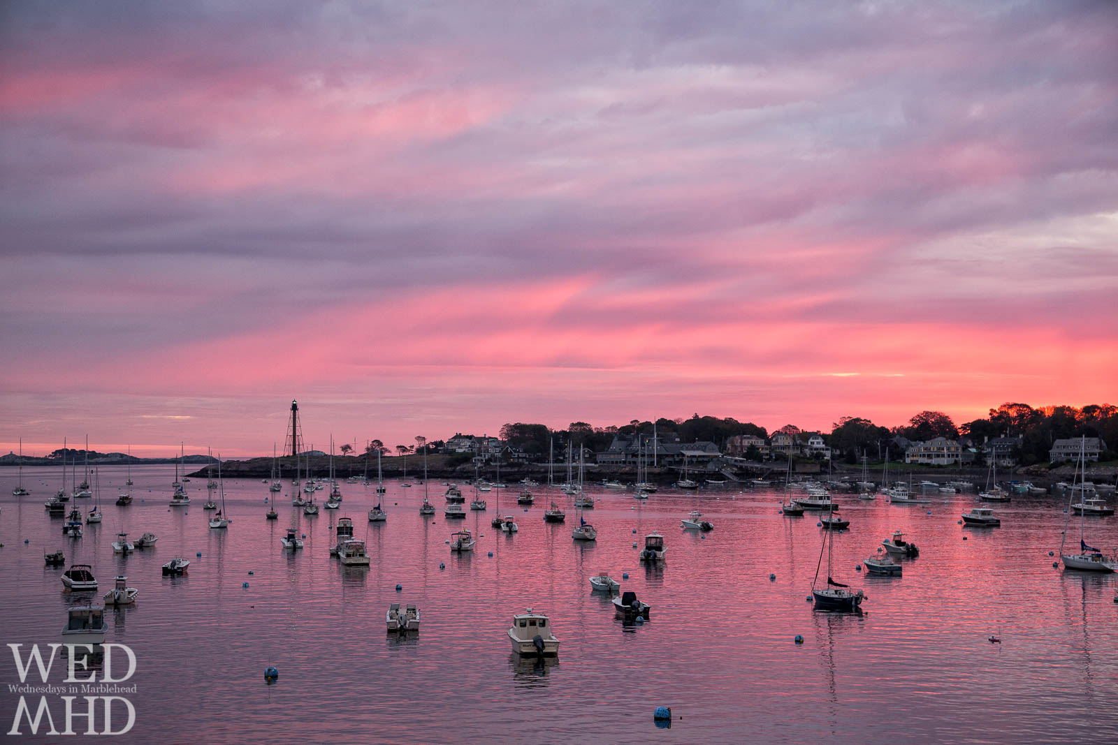 An incredible mix of pinks and purples lights up the sky on a Marblehead Harbor dawn with boats in the harbor all pointing toward Marblehead Light