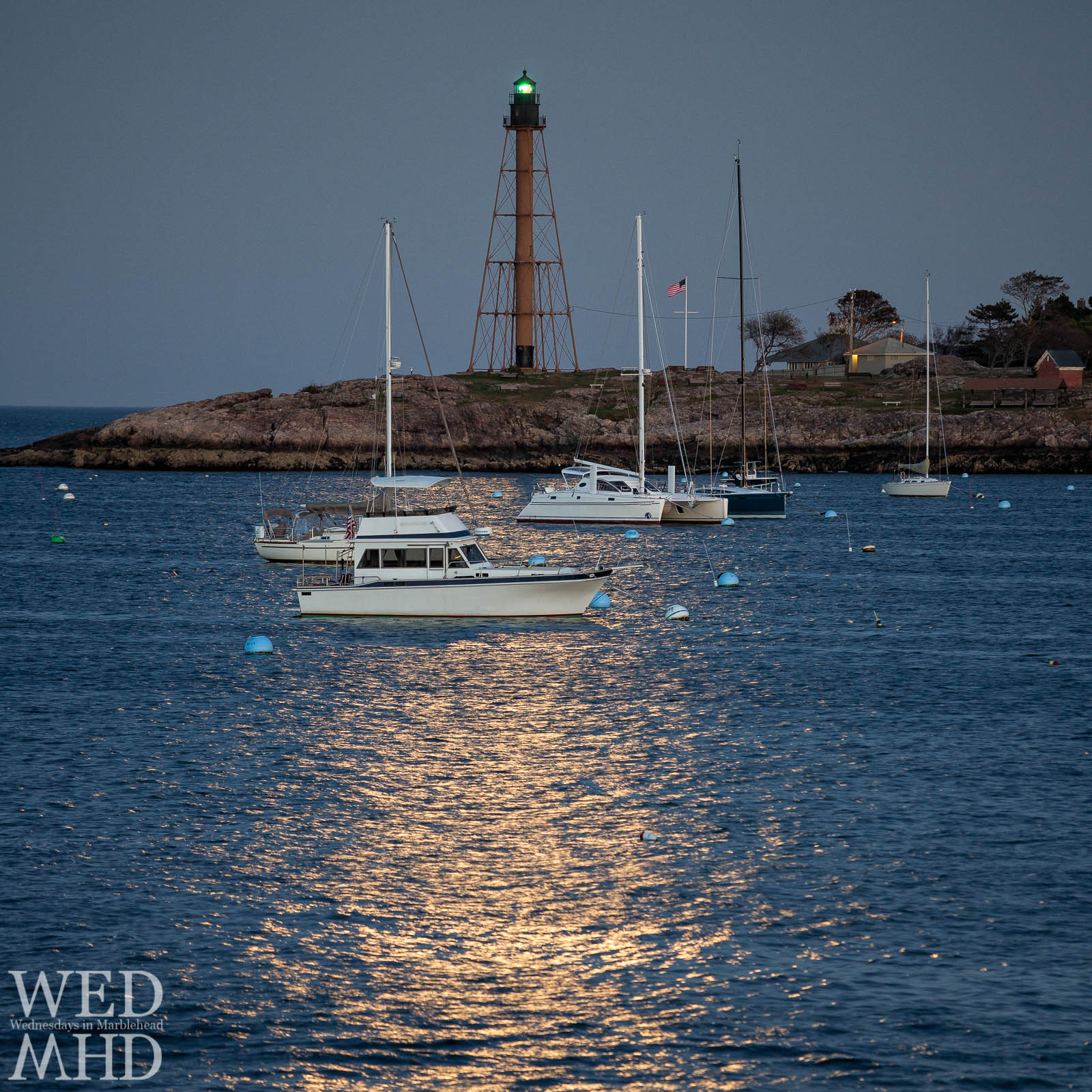 Boats in Marblehead Harbor are moored by moonlight under the light of the Harvest Moon