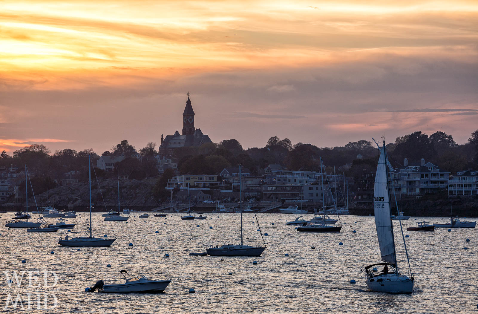 A lone boat heads out at sunset for one last sail in October with Abbot Hall and a few boats setting the backdrop