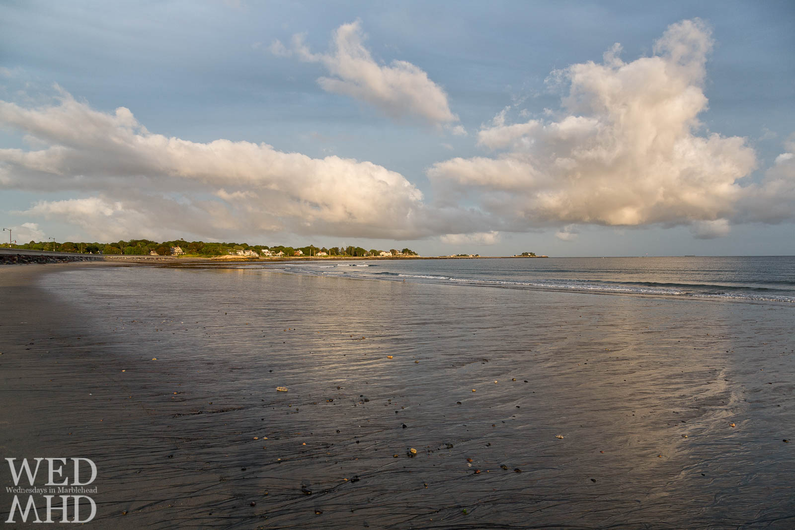 Cumulous clouds shine in late day light and form reflections in the sand at Devereux Beach during low tide