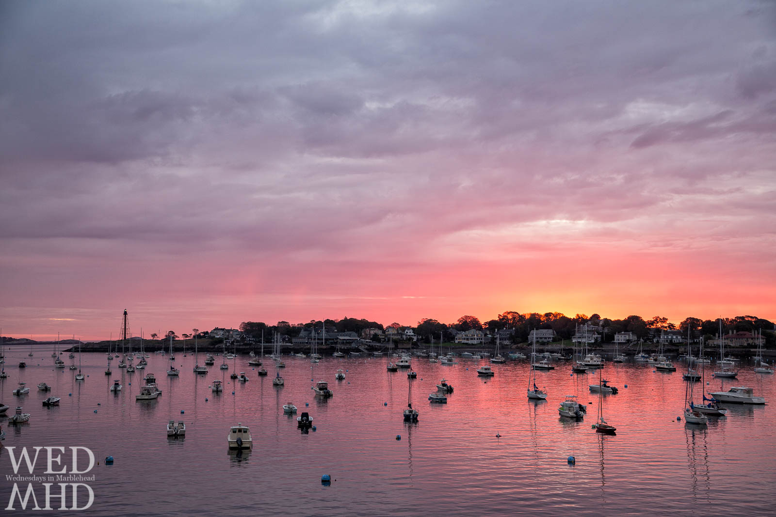 As dawn turns to day the sunrise glow forms over Marblehead Neck illuminating boats moored in the harbor