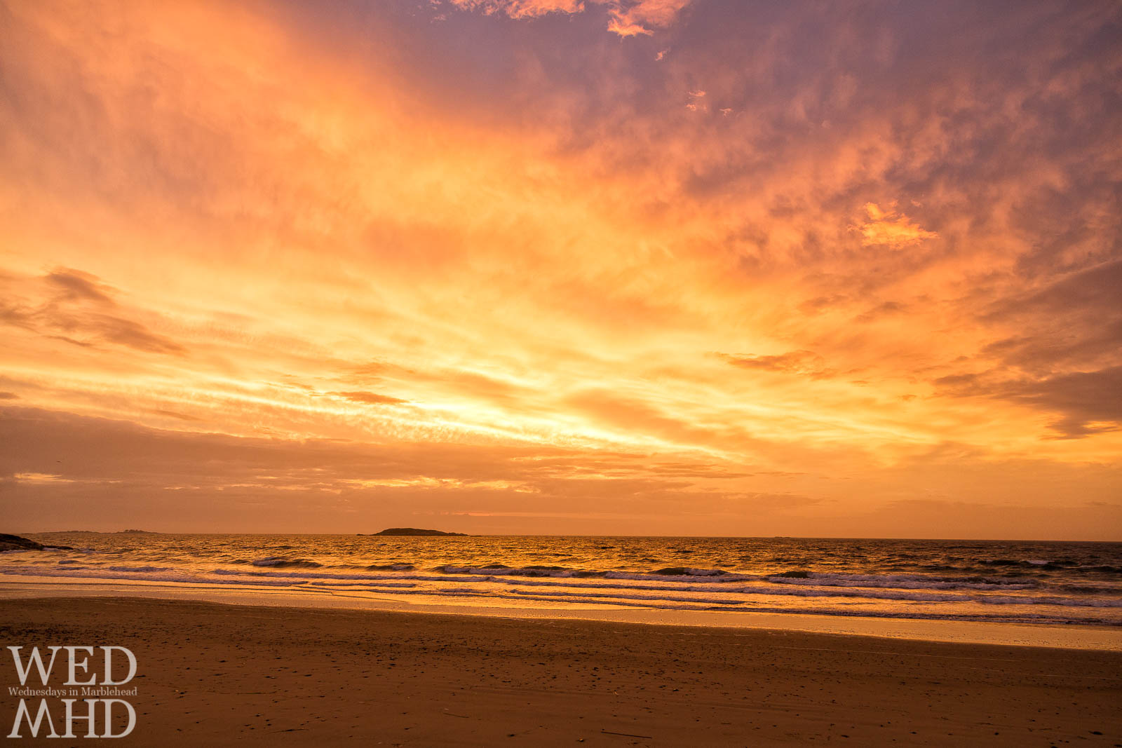 A vibrant golden dawn explodes over the calm waters at Preston Beach on a late October morning
