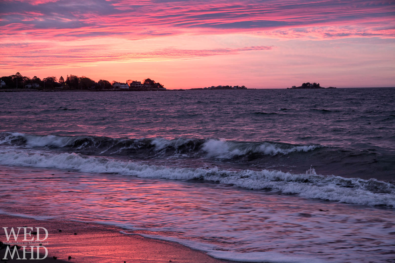 Dawn creates a pink sky over purple waves at Devereux beach in Marblehead