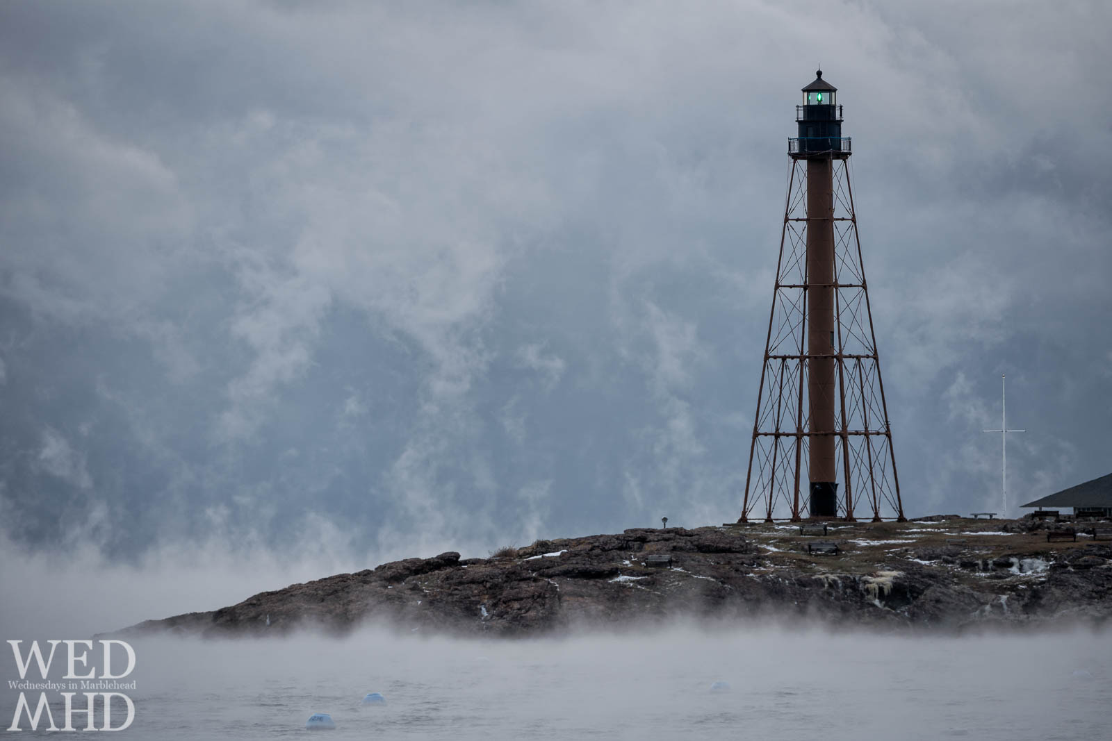 Marblehead Light shines its green beacon in the smoke on an arctic morning