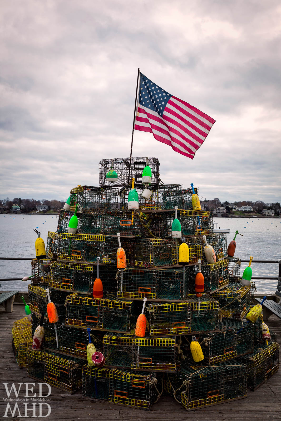 A lobster trap tree is topped by the American flag along Marblehead harbor as a new addition to  the annual Christmas Walk festivities