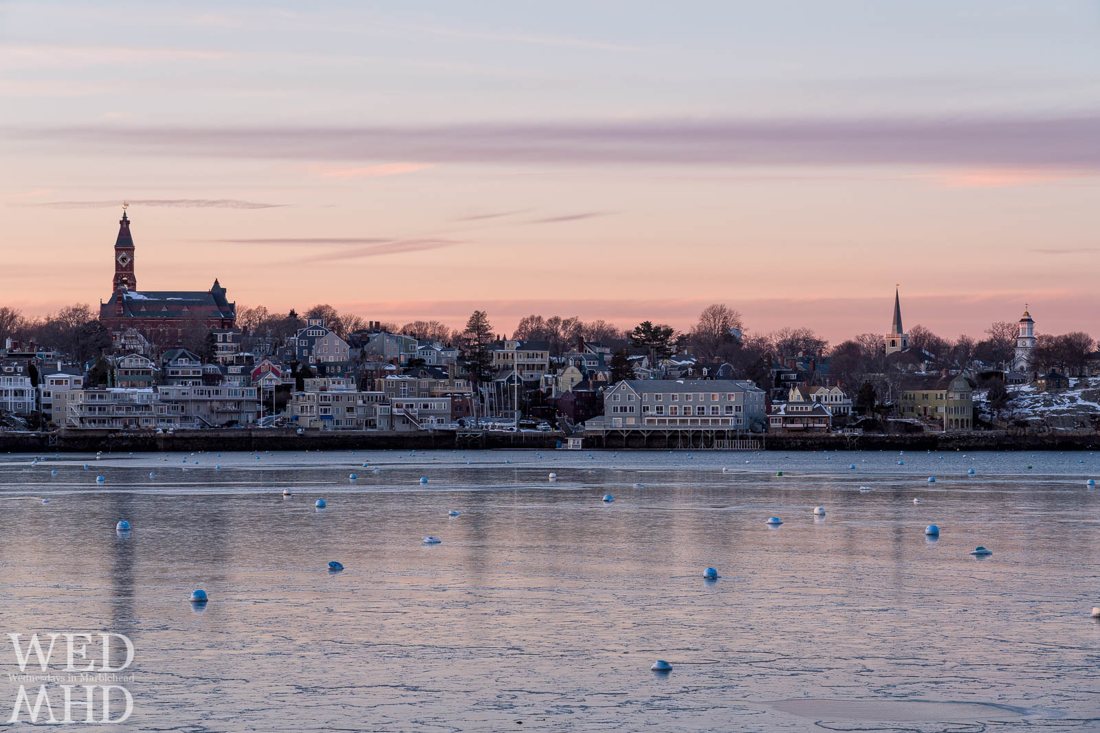 A nearly frozen harbor reflects a beautiful sunset over Marblehead's skyline the night before a blizzard exploded over town