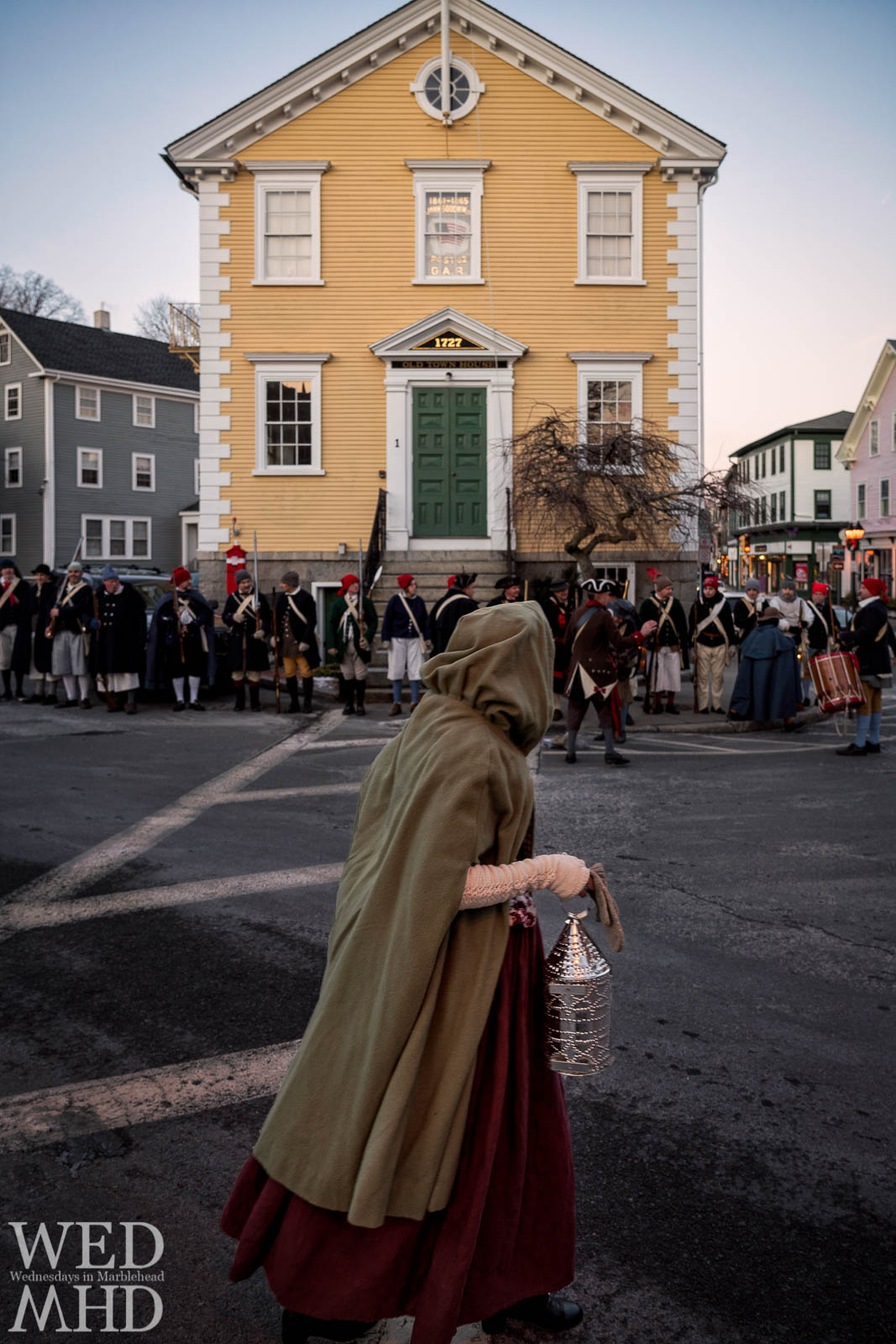 A hooded woman passes by as Glover's Regiment gathers at Old Town House for the annual lantern walk