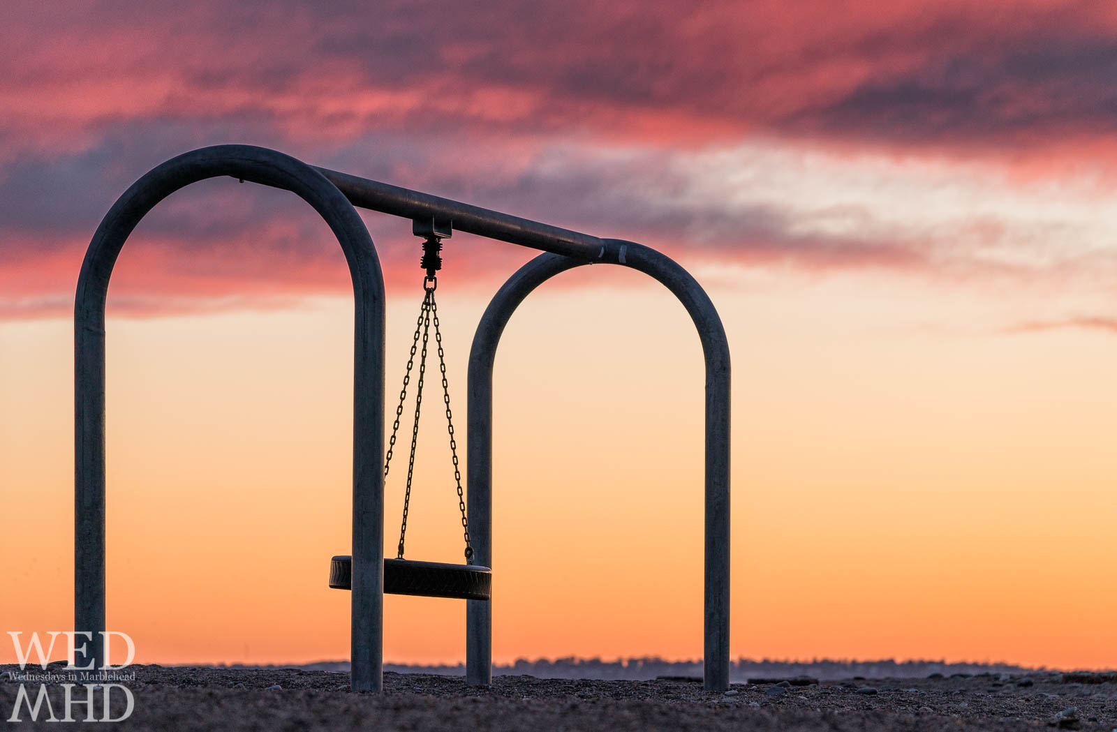 A tire swing stands idle under the sunset sky calling out to kids it's time to play