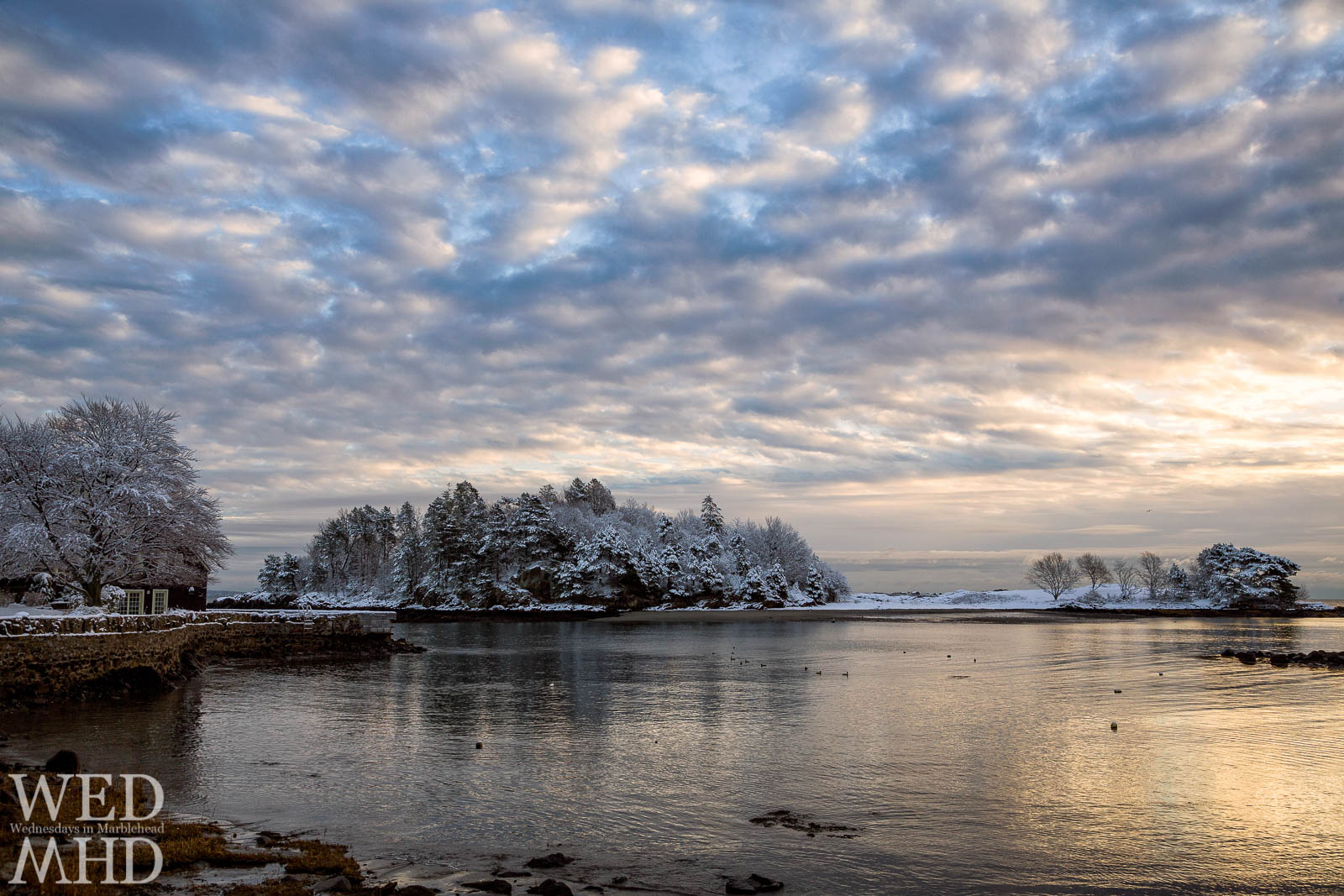 A dusting of snow on Brown's Island shines in the morning light reflected in the waters of Fisherman's Beach