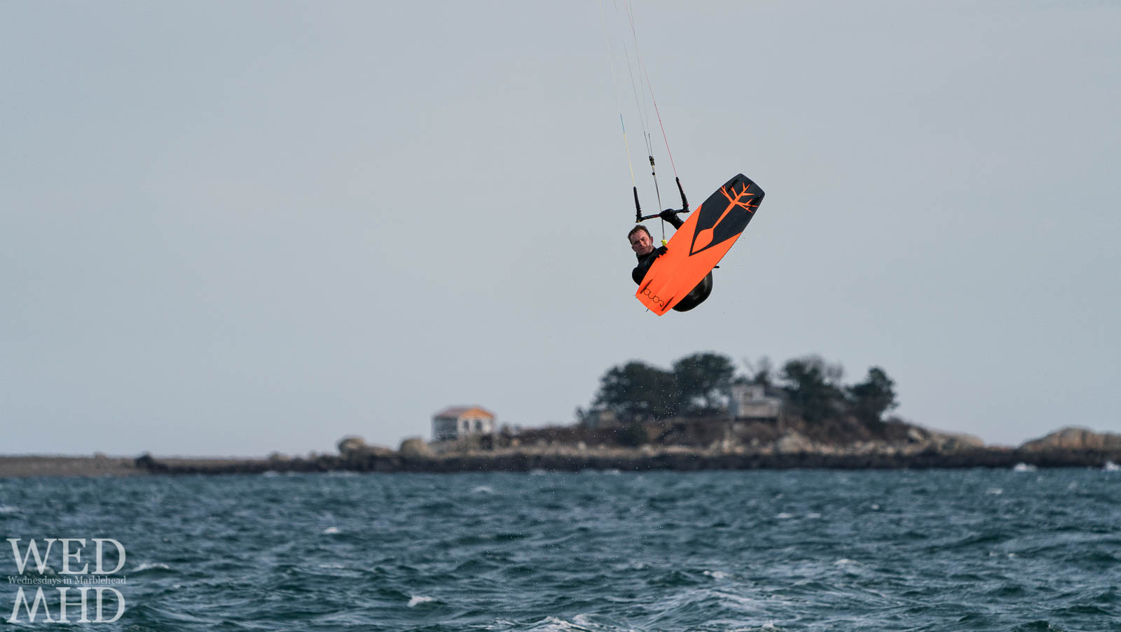 A kite surfer is caught flying over Tinkers Island after catching air on a windy day off Devereux Beach