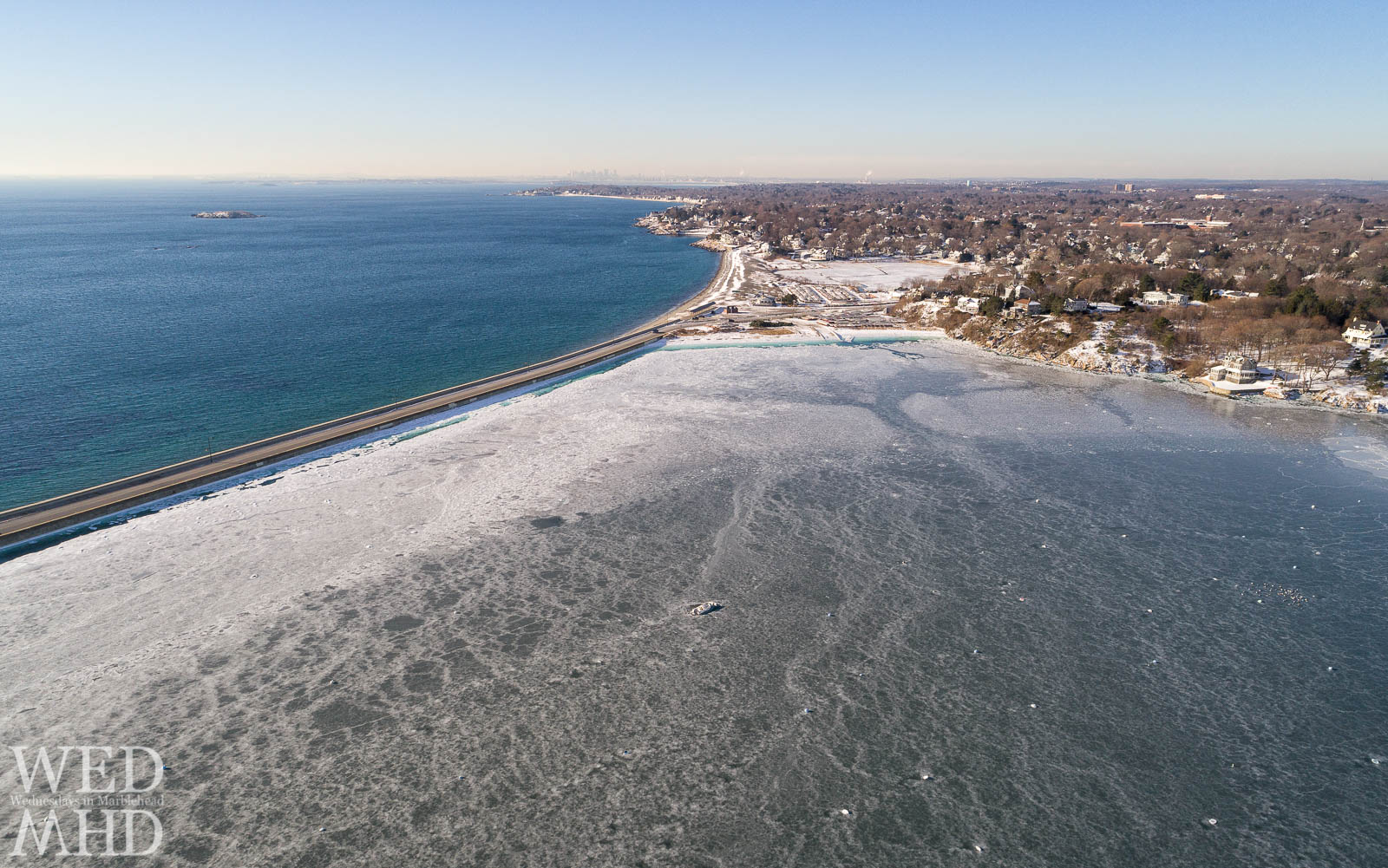 Looking down on a frozen Marblehead Harbor after weeks of arctic conditions reveals a boat trapped in the ice. The ice is contrasted with the deep blue ocean water.