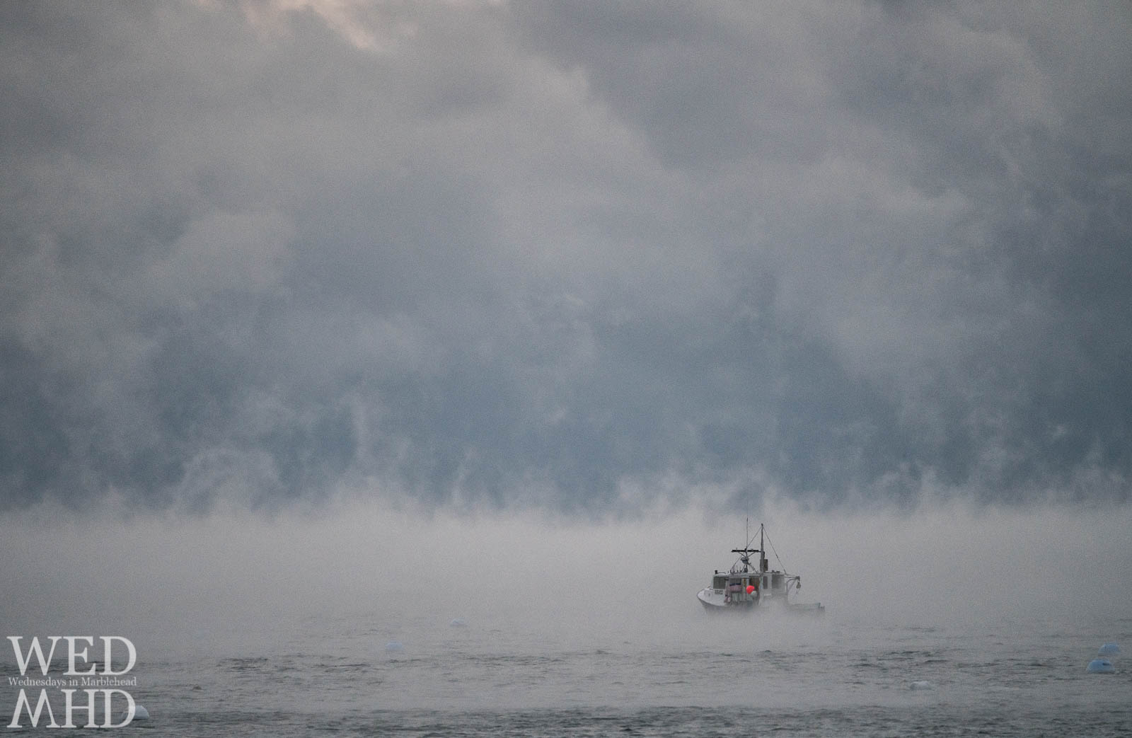 Lobster boat heads into the smoke on an artic morning in December