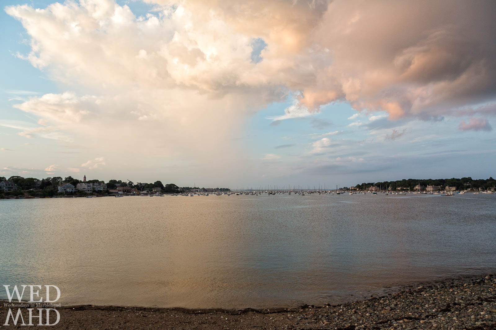 Looking out at Marblehead Harbor from the rocky shore of Riverhead Beach on a mid-August evening reveals numerous boats under a glowing sky