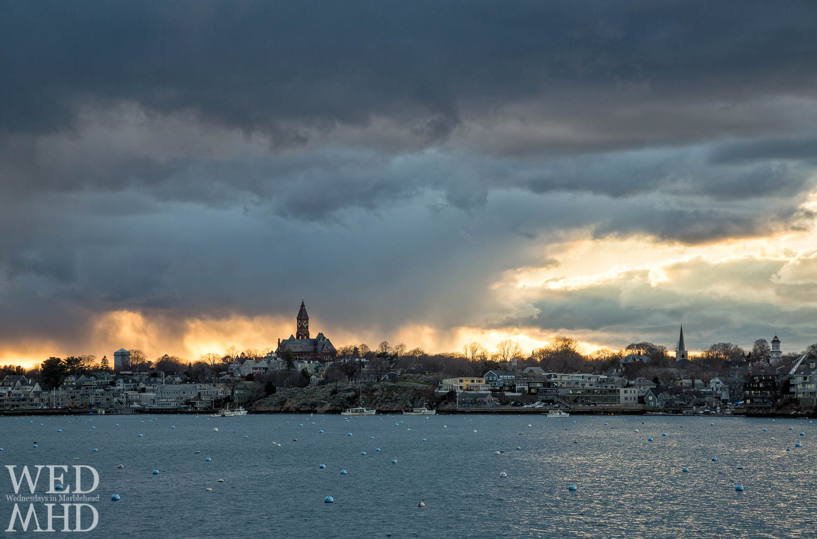 A view across Marblehead Harbor of a March sunset as it continues to build behind familiar buildings