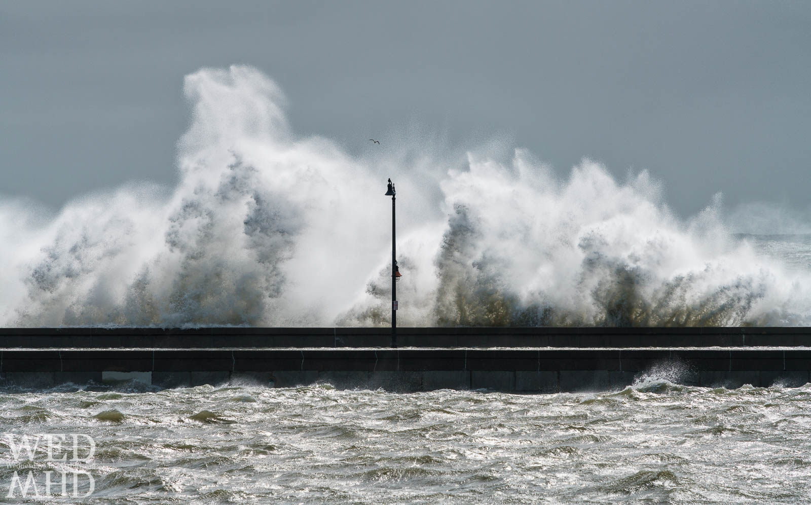 Lamp posts on the causeway help take the measure of a storm as the crashing waves reach over and above the full height of the post at high tide