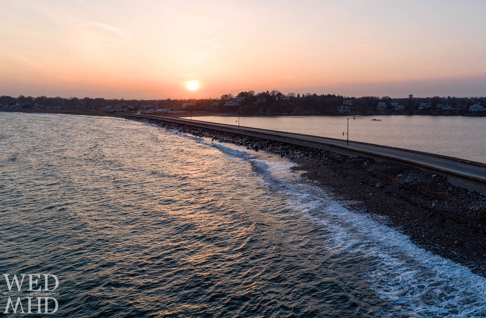 A golden sunset reflects on the Atlantic Ocean in this aerial view over the causeway