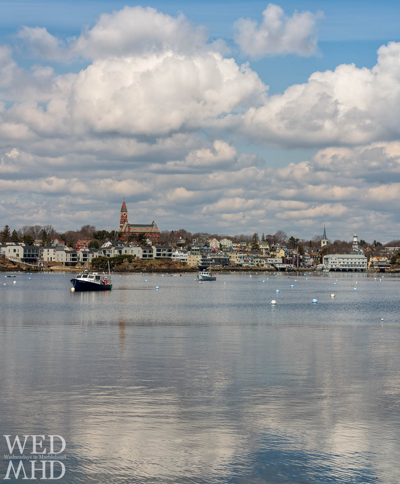 Clouds build and reflect in the still waters of Marblehead Harbor at Noon on an mid-April day