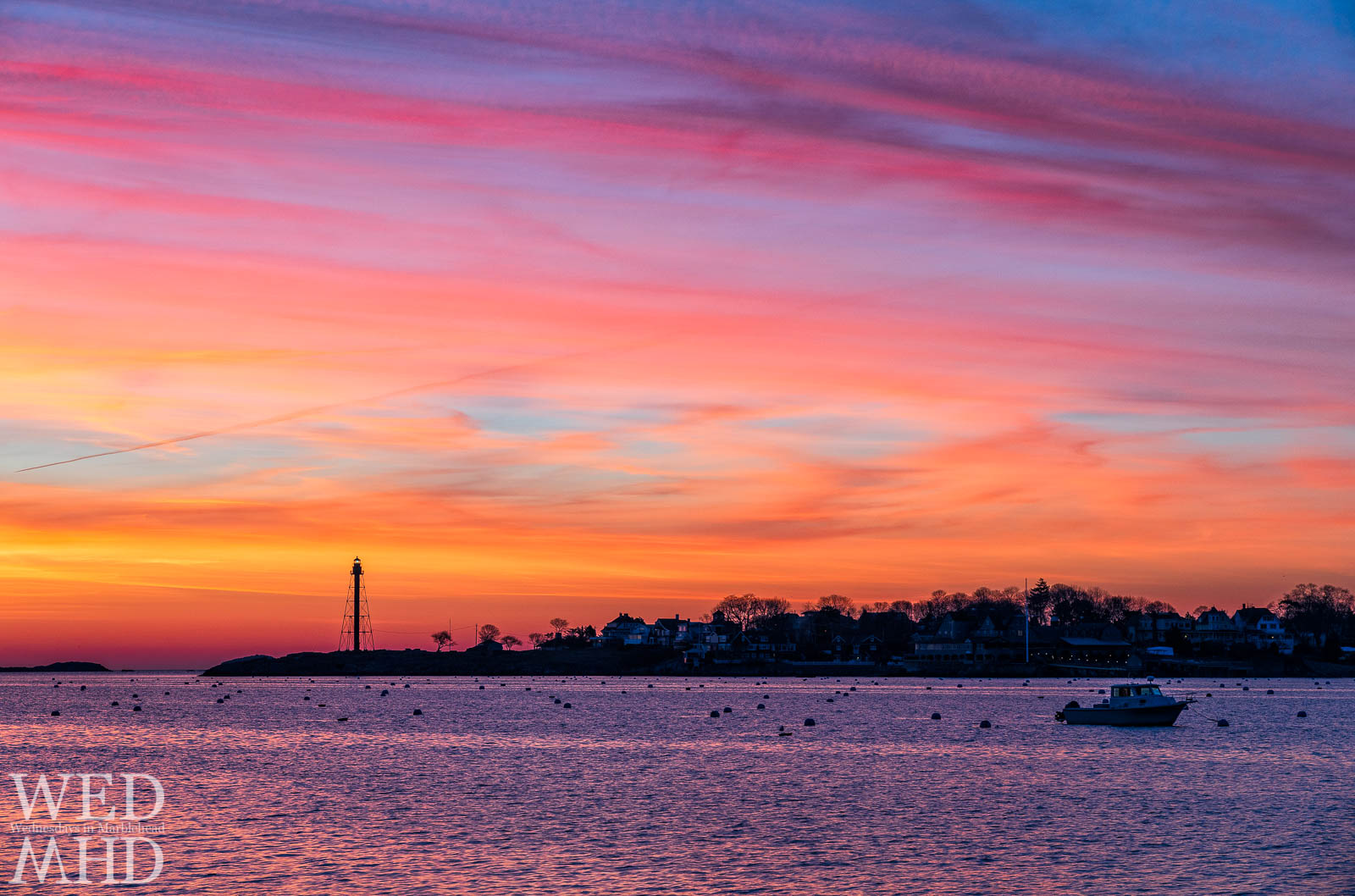Orange, pink and purple light paints the sky and Marblehead Harbor in dawns early light