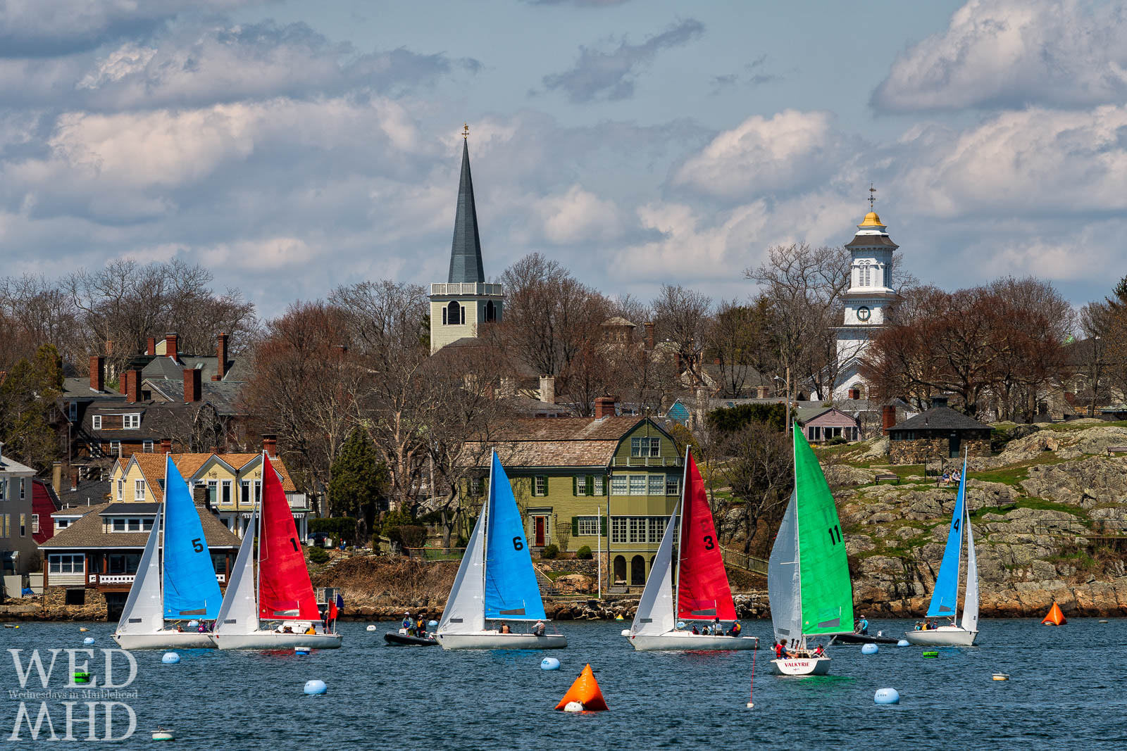 One design boats race for the Jackson Cup in front of the St. Michaels Steeple and Grace Community Church