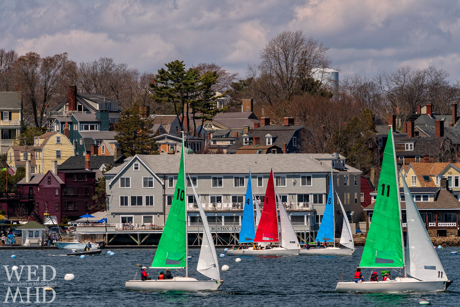 The Jackson Cup race takes place in front of the Boston Yacht Club with sailboats crisscrossing through Marblehead Harbor.