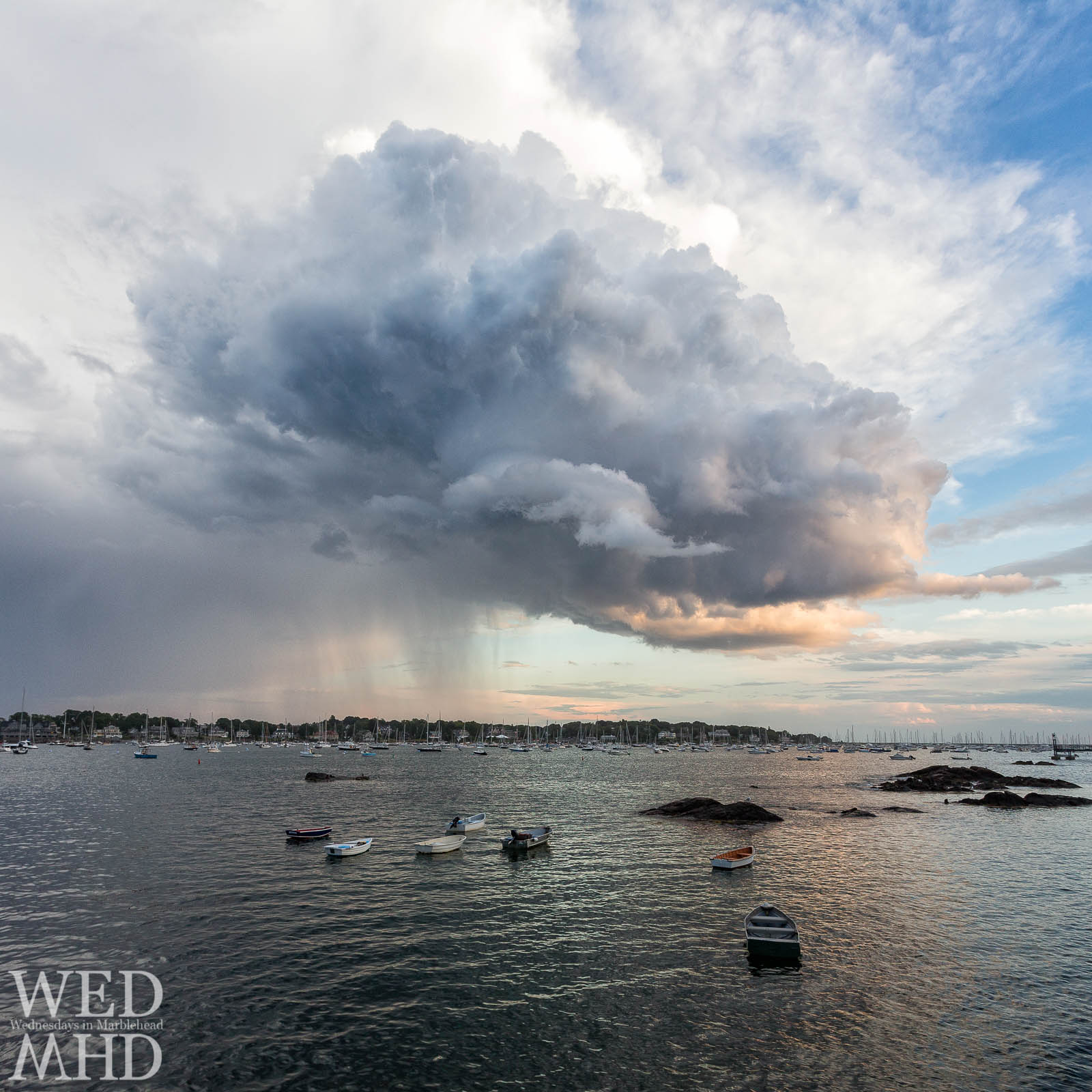 Marblehead Neck is drenched by a rain cloud at sunset whose dramatic structure draws in the viewer's eye